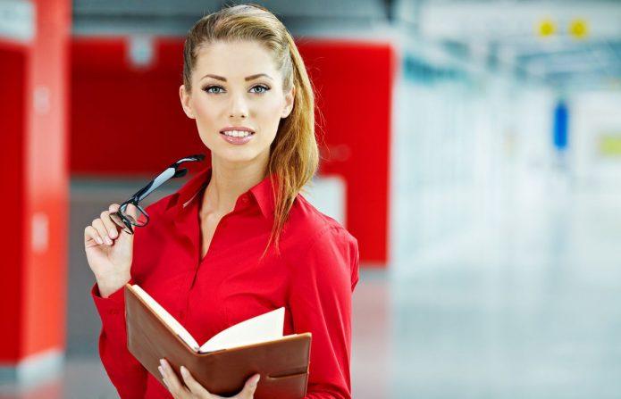 девушка в красной рубашке с ежедневником в руках