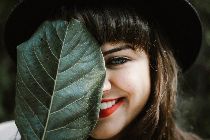 девушка прикрывает лицо и улыбается