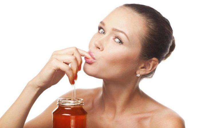 Девушка ест мёд
