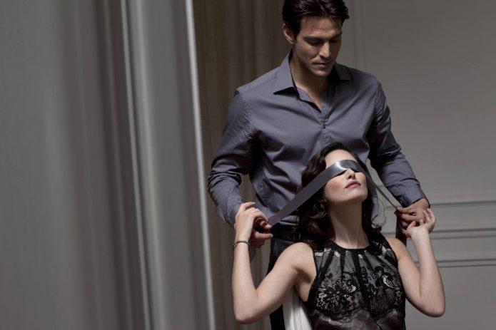 Мужчина завязывает женщине глаза атласной лентой