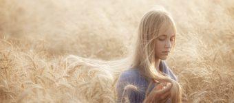 Девушка идёт по полю овса