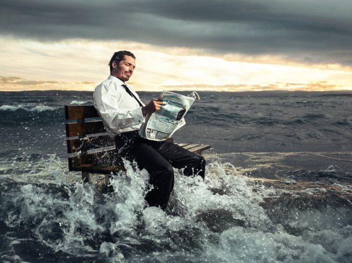 Мужчина спокойно сидит на лавке во время наводнения