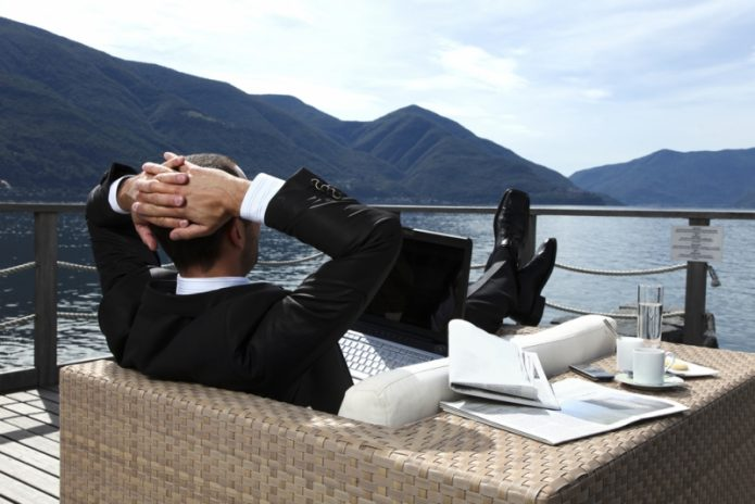 Бизнесмен в костюме на отдыхе у реки