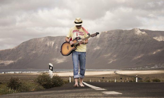 Мужчина босиком идет по дороге и играет на гитаре
