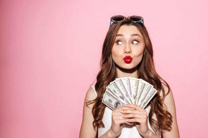 девушка с деньгами на розовом фоне