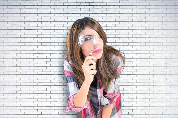 девушка с лупой на фоне кирпичной стены