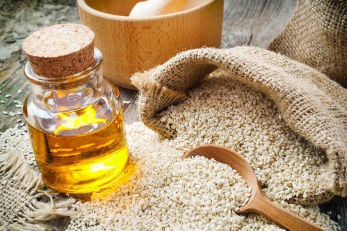 семена кунжута в льняном мешке, кунжутное масло в прозрачном сосуде
