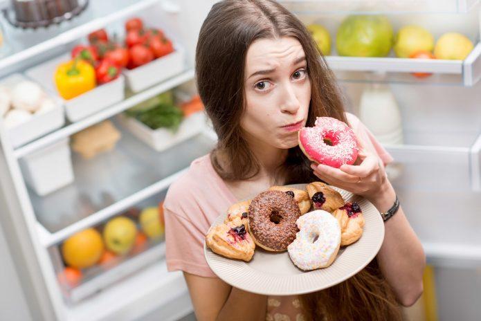 девушка возле холодильника объедается пирожными