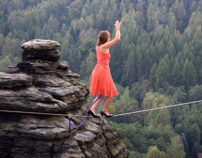 девушка в платье и на каблуках идёт над пропастью по верёвке