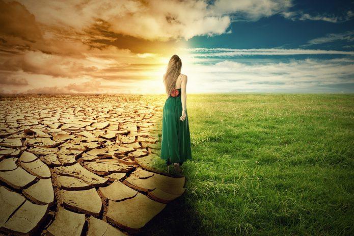 девушка между пустынной землей и зеленой травой