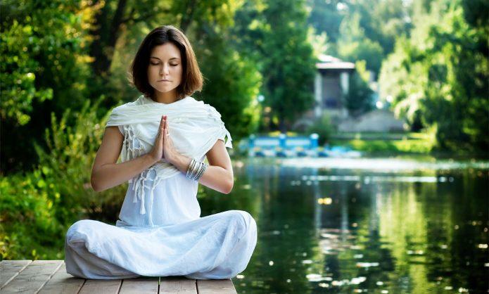 девушка медитирует на причале