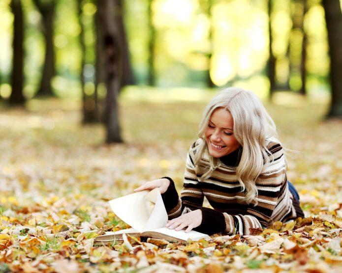 девушка с книгой лежит на осенней листве