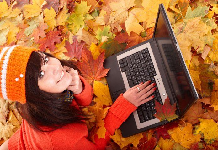 девушка с ноутбуком в осенней листве