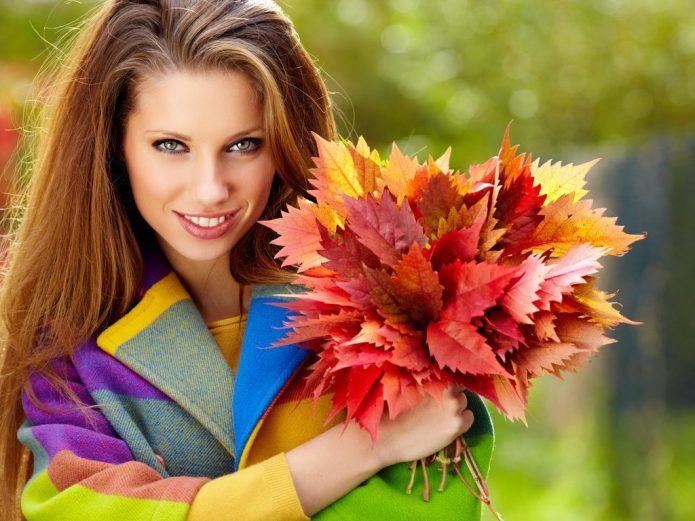 девушка в ярком пальто с букетом из осенних листьев
