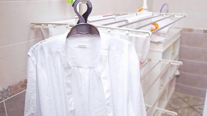 Белая рубашка сушится на плечиках