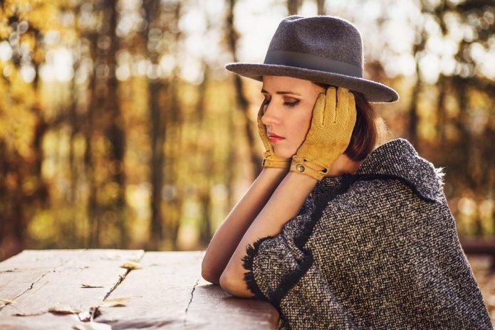 девушка в шляпе закрыла гласа и прикрыла уши руками, осень