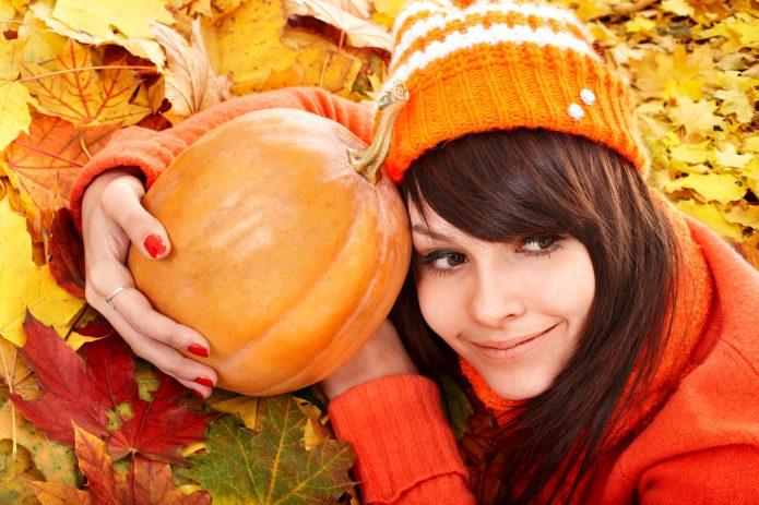 девушка с тыквой лежит на осенней листве
