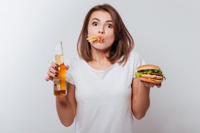 Девушка с гамбургером, картошкой фри и пивом