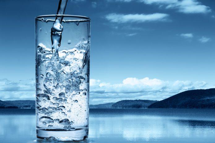 Стакан с минеральной водой на фоне озера