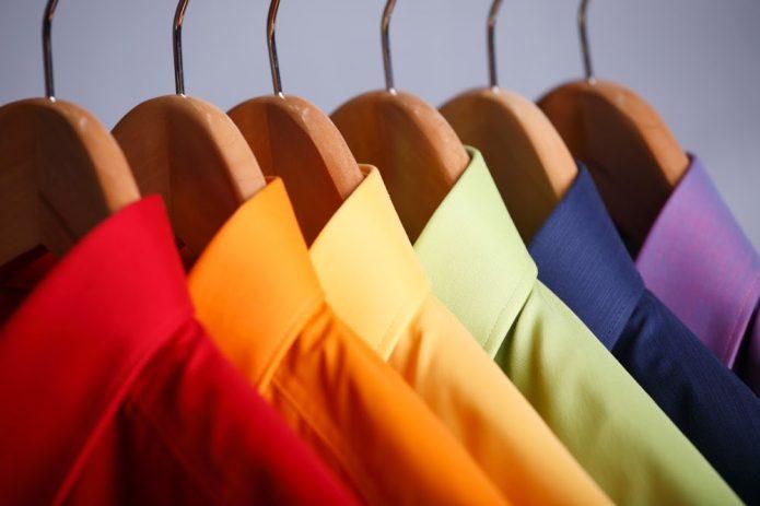 Разноцветные рубашки на деревянных плечиках