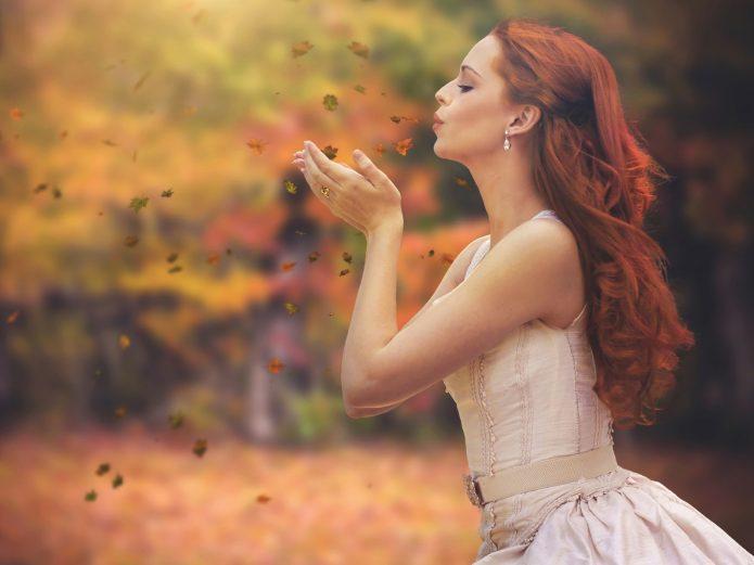 девушка дует на осенние листья