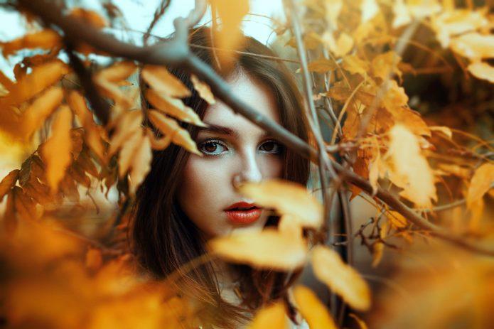 девушка за осенней листвой