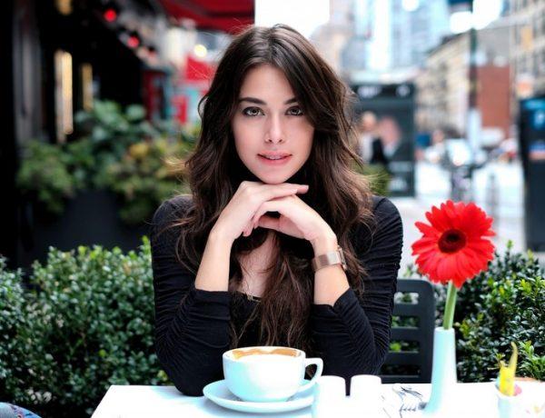 Девушка за столом, чашка кофе и гербера