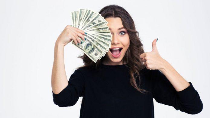 радостная девушка с деньгами на белом фоне