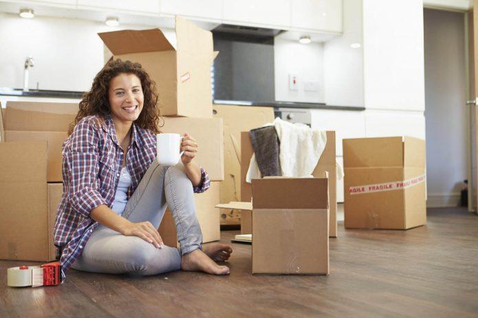 девушка с чашкой среди коробок, переезд