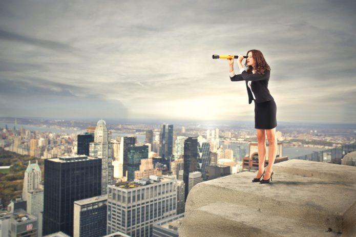 девушка в деловом костюме с подзорной трубой на крыше