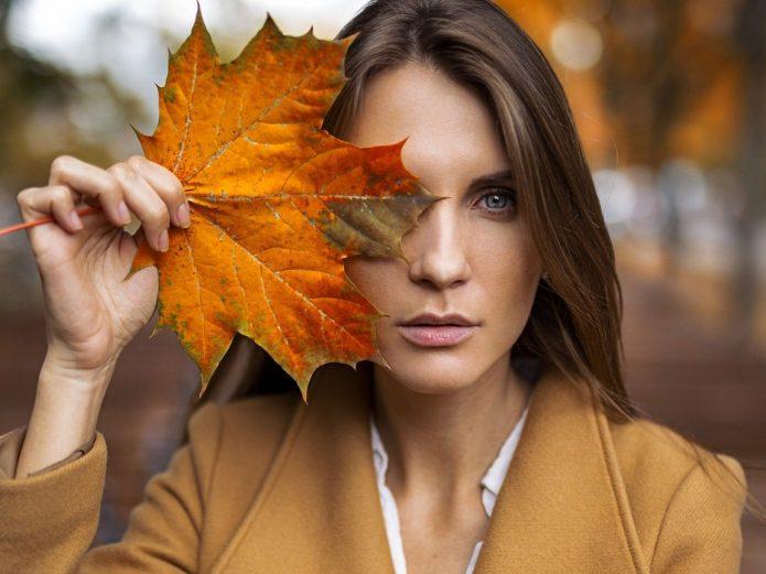 девушка прикрыла глаз осенним кленовым листком