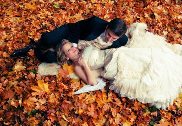 молодожёны лежат на осенней листве