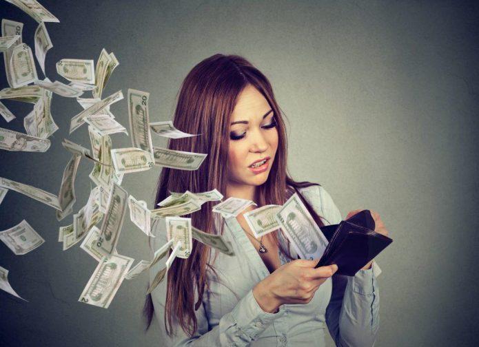 деньги улетают из кошелька, разочарованная девушка