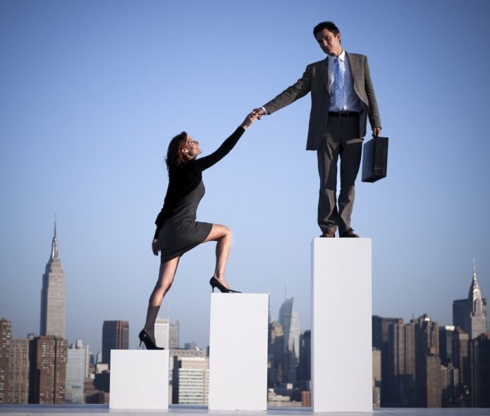 Мужчина помогает женщине взобраться на карьерную лестницу
