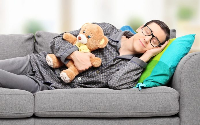 Мужчина спит на диване с медвежонком в руке