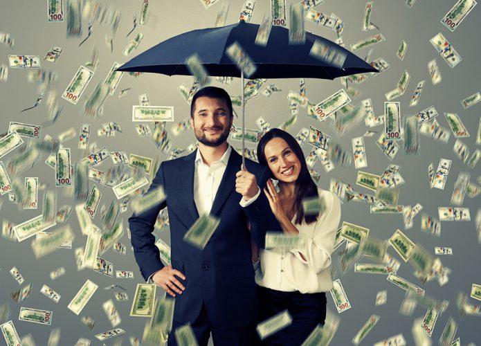 мужчина и женщина с зонтом под денежным дождём