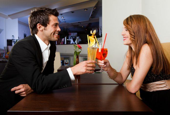 мужчина и женщина с коктейлями, столик в кафе