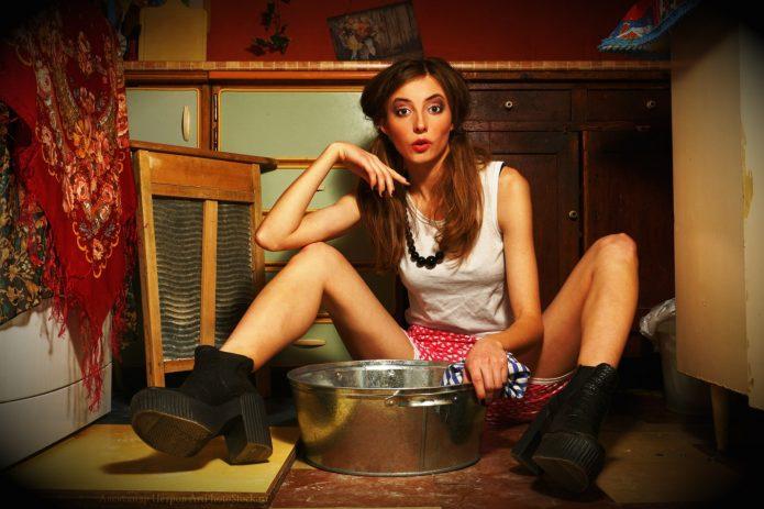 Девушка сидит с металлическим тазом между ног