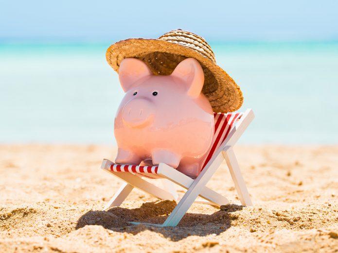 Свинья копилка в шезлонге на пляже