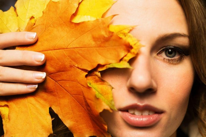 девушка прикрыла половину лица осенним кленовым листом