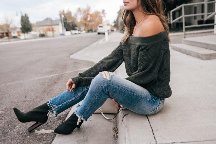 Свитер со спущенными плечами и рваные джинсы