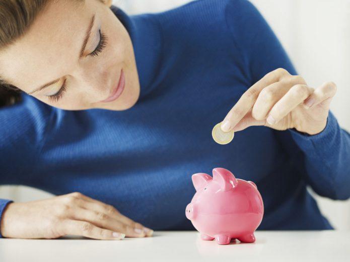 девушка кладёт монету в свинку-копилку