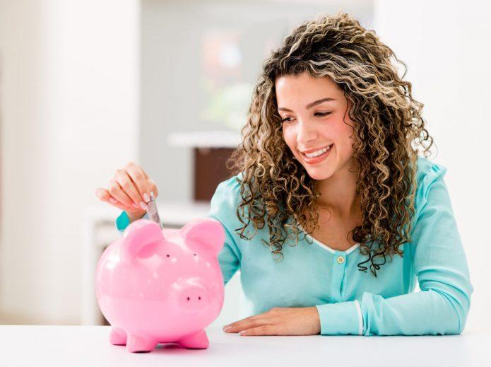 девушка кладёт купюру в свинку-копилку