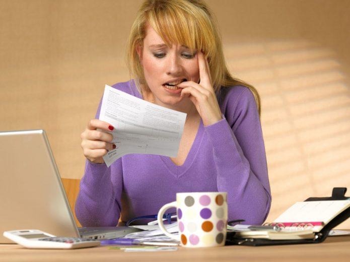 озадаченная женщина читает документ, кружка, ноутбук, ежедневник