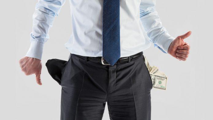 мужчина в деловом костюме с пустым и денежным карманами