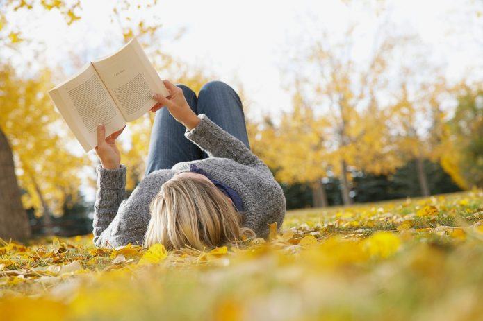 девушка читает книгу на осенней листве