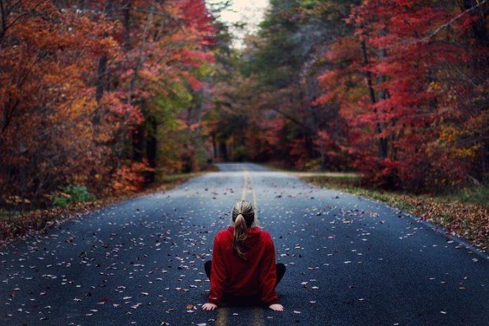 осень, девушка сидит на пустой дороге