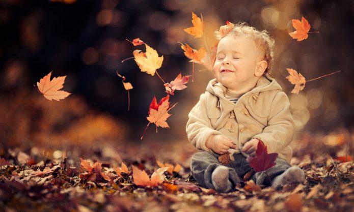 ребёнок в осенних листьях