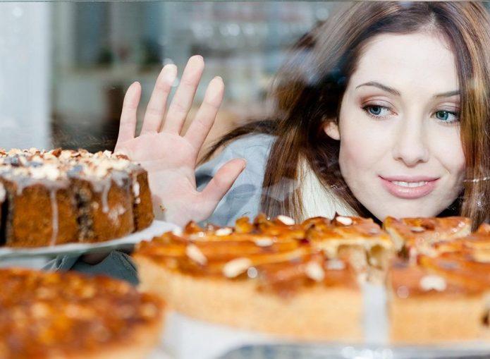 девушка смотрит на выпечку через стекло