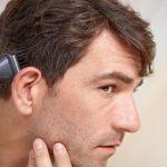 Мужчина пользуется триммером для волос на голове
